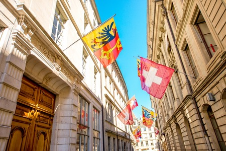 Street view with Swiss flags on the buildings in the old town of Geneva city in Switzerland