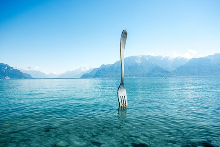 Vevey, Switzerland - June 23, 2016: The fork sculpture in Geneva lake outside the Alimentarium food museum in Vevey. The fork was originally installed in 1995 as a temporary exhibit.