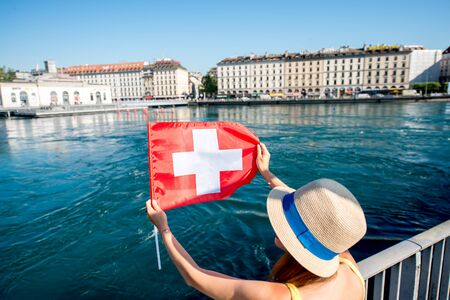 pedestrian bridges: Young female traveler with swiss flag on the pedestrian bridge in the center of Geneva city in Switzerland. Happy vacation in Geneva city