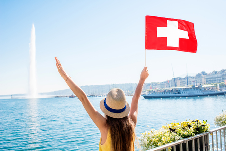 Young female traveler with swiss flag enjoying great view on Geneva lake with famous fountain in Switzerland