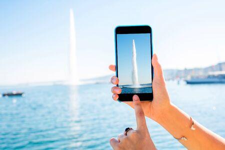 jet stream: Photographing with phone famous jet fountain near Geneva city in Switzerland Foto de archivo