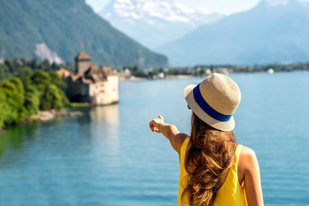 montreux: Young female traveler enjoying great view on Geneva lake with castle on the background in Switzerland Stock Photo