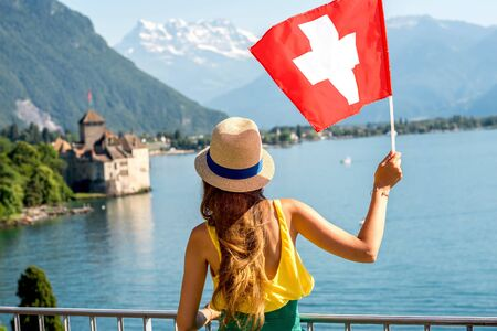 alp: Young female traveler with swiss flag enjoying great view on Geneva lake with castle on the background in Switzerland