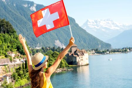 Young female traveler with swiss flag enjoying great view on Geneva lake with castle on the background in Switzerland