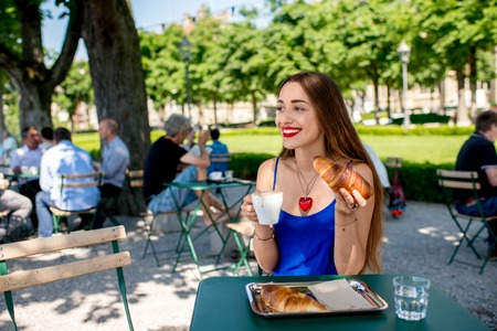 blue dress: Beautiful woman in the blue dress sitting at the cafe with coffee and croissant outdoors at the park.