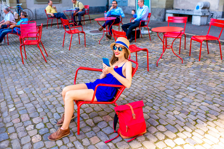 munster: Young female tourist sitting on the red public chairs on Munster square in the old town of Bern city in Switzerland Stock Photo