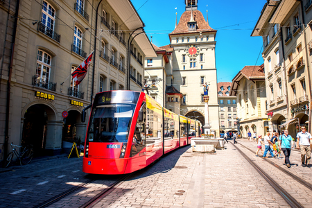 red centre: Bern, Switzerland - June 24, 2016: Street view on Kramgasse with red tram in the old town of Bern city. Kramgasse is a popular shopping street and medieval city centre of Bern, Switzerland Editorial