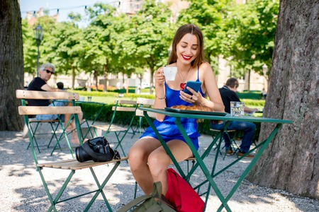 good weather: Beautiful woman in the blue dress sitting at the cafe with coffee and croissant using mobile phone outdoors at the park.