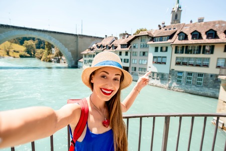 Young female tourist making selfie photo on the old town of Bern city backround in Switzerland. Having a great vacations in Switzerland