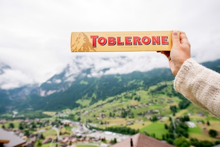Grindelwald, Switzerland - June 26, 2016 Female hand holds Toblerone chocolate on the mountains background in Switzerland. Toblerone is a famous Swiss chocolate bar brand