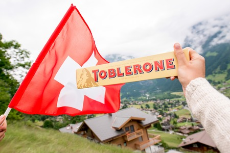 toblerone: Grindelwald, Switzerland - June 26, 2016 Female hand holds Toblerone chocolate with swiss flag on the mountains background in Switzerland. Toblerone is a famous Swiss chocolate bar brand Editorial
