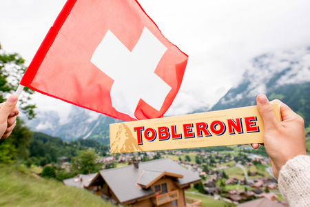 Grindelwald, Switzerland - June 26, 2016 Female hand holds Toblerone chocolate with swiss flag on the mountains background in Switzerland. Toblerone is a famous Swiss chocolate bar brand Editorial