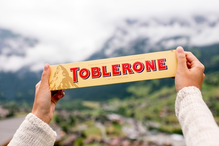 toblerone: Grindelwald, Switzerland - June 26, 2016 Female hand holds Toblerone chocolate on the mountains background in Switzerland. Toblerone is a famous Swiss chocolate bar brand