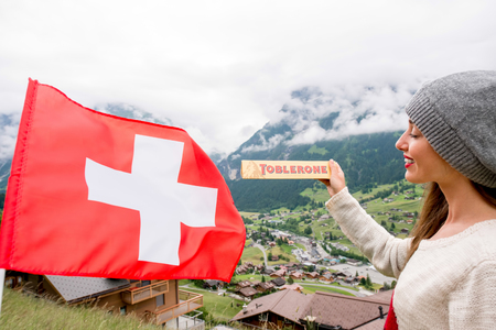 toblerone: Grindelwald, Switzerland - June 26, 2016 Young woman holds Toblerone chocolate with Swiss flag on the mountains background in Switzerland. Toblerone is a famous Swiss chocolate bar brand