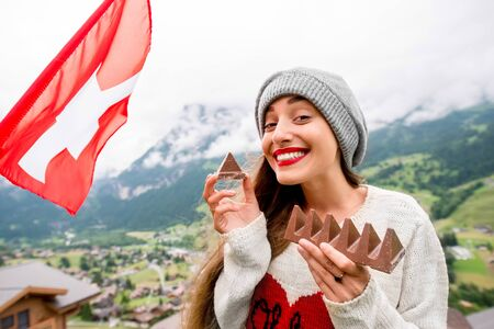 Young woman with swiss flag eating chocolate outdoors in the mountains. Having great vacations in Switzerland Stockfoto