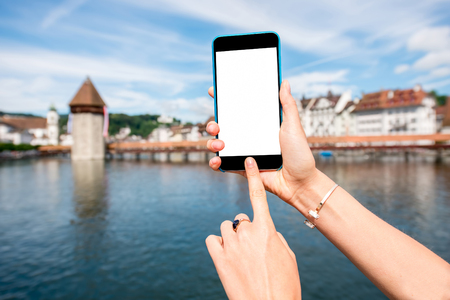Holding a smart phone with empty screen on Lucerne city backgound in Switzerland