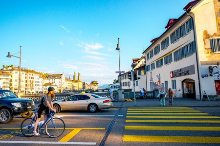 Zurich, Switzerland - June 28, 2016: Street view on Rudolf Brun bridge with cars, woman on the bicycle and people on the crossing in Zurich old town in Switzerland Editorial