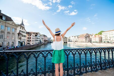 Female tourist enjoying cityscape view on the old town of Zurich city. Woman having happy vacations in Switzerland