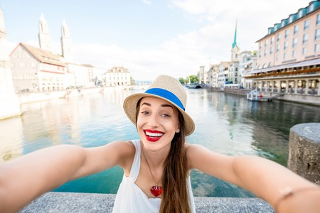 Young female tourist making selfie photo with cityscape view on the river and old town in Zurich city. Having happy vacations in Switzerland Stock Photo