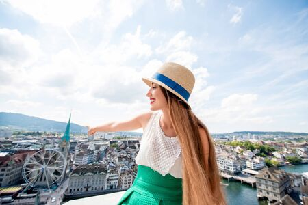 Young female tourist sitting on the top of the church tower in Zurich city. Woman having a great vacation in Switzerland