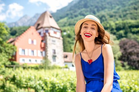 A portrait of a young female tourist near famous red house in Vaduz town in Liechtenstein Stock Photo