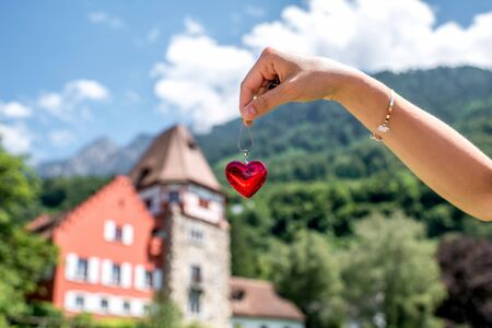 Holding a red pendant in form of the heart with red house on the background in Vaduz town in Liechtenstein