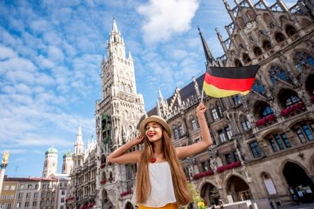 Portrait eines jungen weiblichen Touristen mit Deutsch Flagge, die auf dem zentralen Platz vor dem Rathaus in München. Mit einem schönen Urlaub in Deutschland Standard-Bild - 66316838