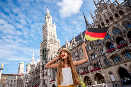 Portrait of a young female tourist with german flag standing on the central square in front of the town hall building in Munich. Having a great vacation in Germany Stockfoto
