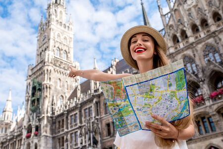 Portrait of a young female tourist with map standing on the central square in front of the famous town hall building in Munich Stock Photo