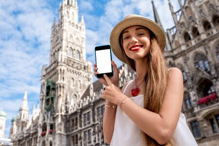 Young woman showing phone with white screen on the town hall building background in Munich 版權商用圖片