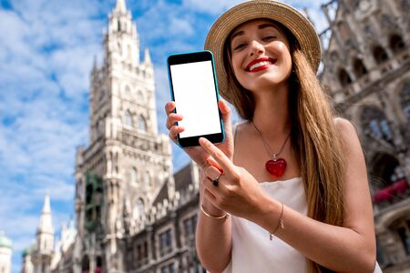 hall monitors: Young woman showing phone with white screen on the town hall building background in Munich Stock Photo