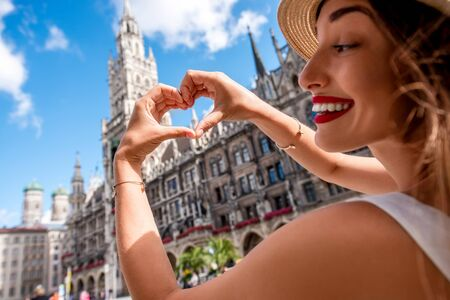 Young female tourist making heart shape with hands on the town hall building background in Munich. Having a great vacation in Germany Stock Photo