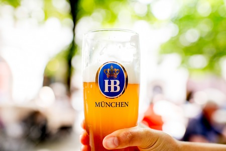 state owned: Munich, Germany - July 03, 2016: Famous bavarian Hofbrauhaus beer in the glass outdoors on the blurred background. Hofbrauhaus is a brewery in Munich, owned by the Bavarian state government. Editorial