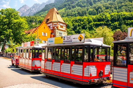 Vaduz, Liechtenstein - July 01, 2016: People on the tourist train visit famous red house with wineyard in Vaduz city. This house is very popular tourist attraction in Liechtenstein Editorial