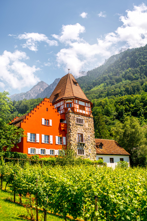 Vaduz, Liechtenstein - July 01, 2016: Famous red house with wineyard owned by the Rheinberger family in Vaduz city, Liechtenstein. This house is very popular tourist attraction in Liechtenstein