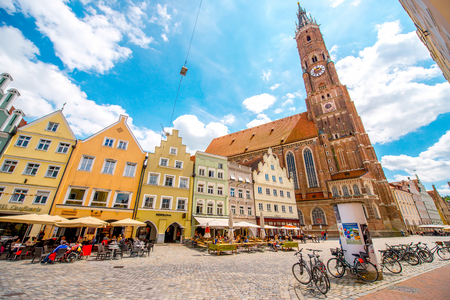 landshut: Landshut, Germany - July 04, 2016: Street view with elder woman ride a bicycle in the center of Landshut old town in Germany