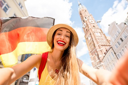 landshut: Young female tourist with german flag making selfie photo on the bavarian old town background with saint Martin church in Landshut.