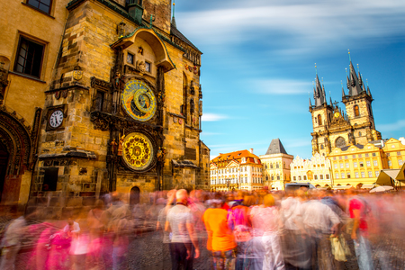 Uitzicht op de astronomische klok en de kathedraal op het oude stadsplein in Praag. Lange image blootstelling techniek met vage mensen en wolken