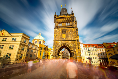 View on the tower of Charles bridge in the old town of Prague city. Long exposure image technic with blurred people and clouds