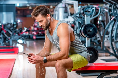 Muscular man using mobile phone sitting on the bench after the training in the gym Stock Photo