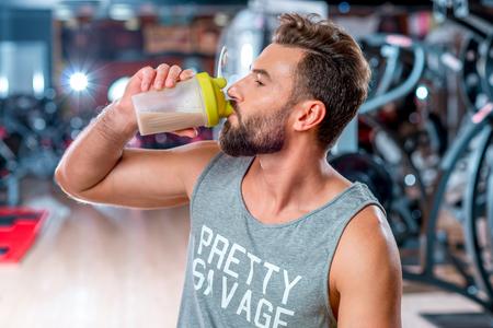 Gespierde man drinken sportvoeding zit met halter in de sportschool