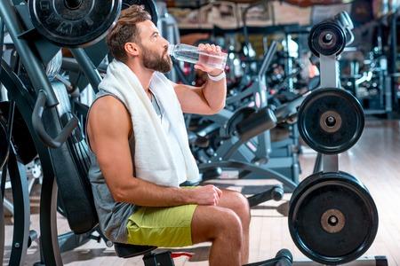 man drinking water: Sport man drinking water in the gym