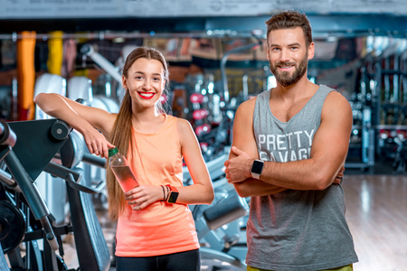 Portrait of young sports couple standing in the gym. Personal trainer with young girl Reklamní fotografie