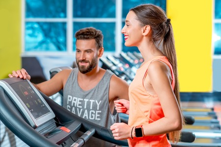 Sports woman making cardio workout on stationary treadmill with personal trainer or friend in the gym with window on the background.