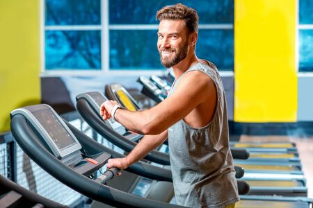 cardio workout: Portrait of handsome man making cardio workout on stationary treadmill in the gym.