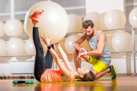 fitball: Young woman making exercise with fitball with personal trainer in the fitness room