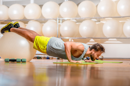 fitball: Sports man making push-ups with fitball in the fitness room