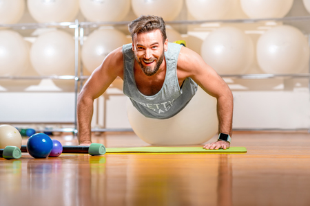 fitball: Smiling sports man making push-ups with fitball in the fitness room