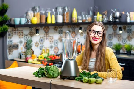 cocktail mixer: Portrait of young woman sitting on the table with fresh greens and blender at home Stock Photo