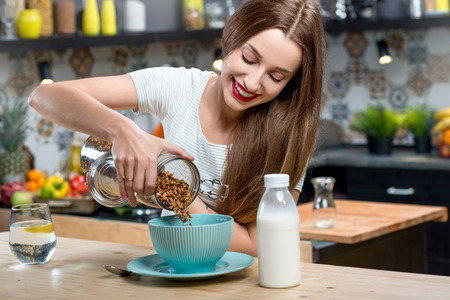 Young woman making breakfast with granola and milk in the modern kitchen at home Stock Photo